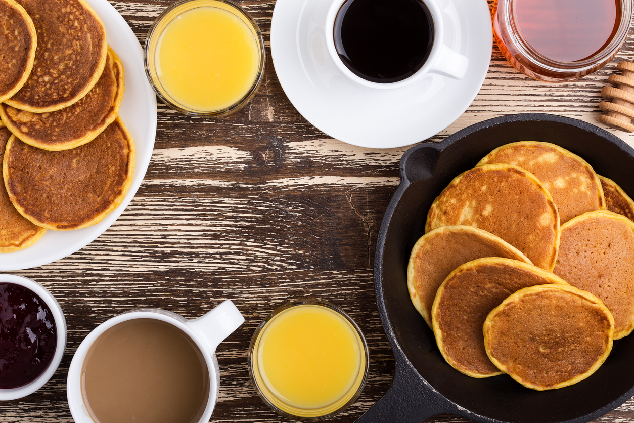 Pumpkin pancakes breakfast or brunch. Homemade pancakes with berry jam and honey, orange juice and cup of coffee. Table viewed from above