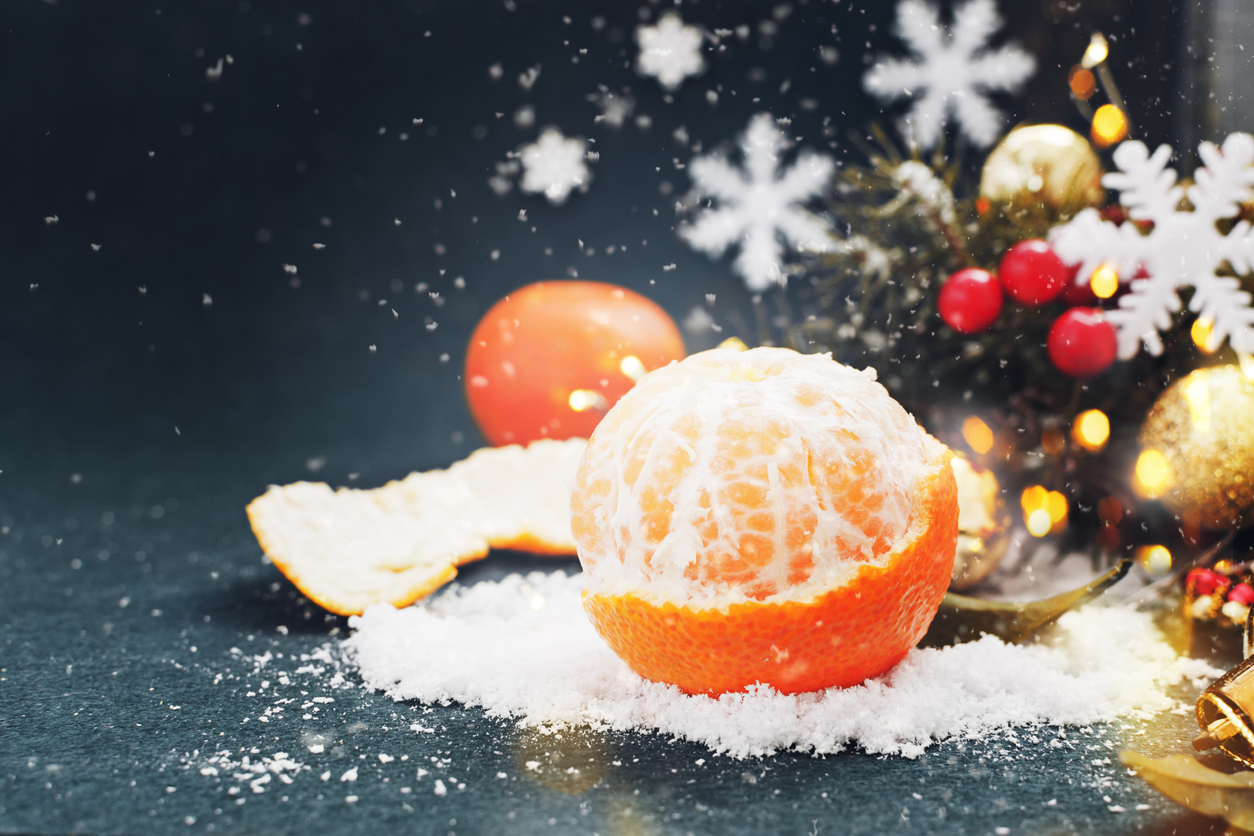 Tangerine with snow in Christmas decor on the dark blue background.